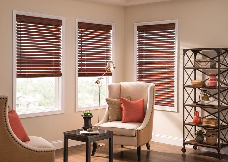 Sitting room with three windows featuring wood blinds.