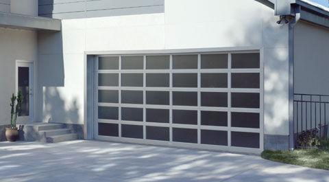 Home featuring a dark grey aluminum full veiw specialty door. Ornamental Iron Garage doors available too.