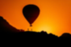 A hot air balloon flys in Cappadocia over a mountain, while two people stand right beneath him.