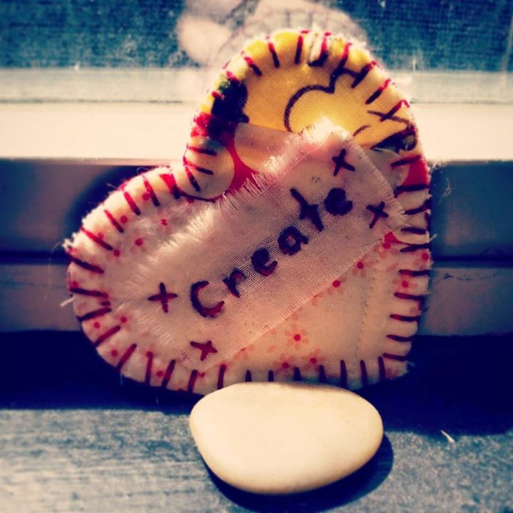 """fabric heart shaped patch that says, """"create"""" leaning against a window sill with a smooth, flat rock in front of it"""