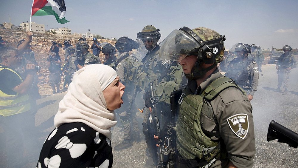 A Palestinian woman argues with an Israeli border policeman in the West Bank
