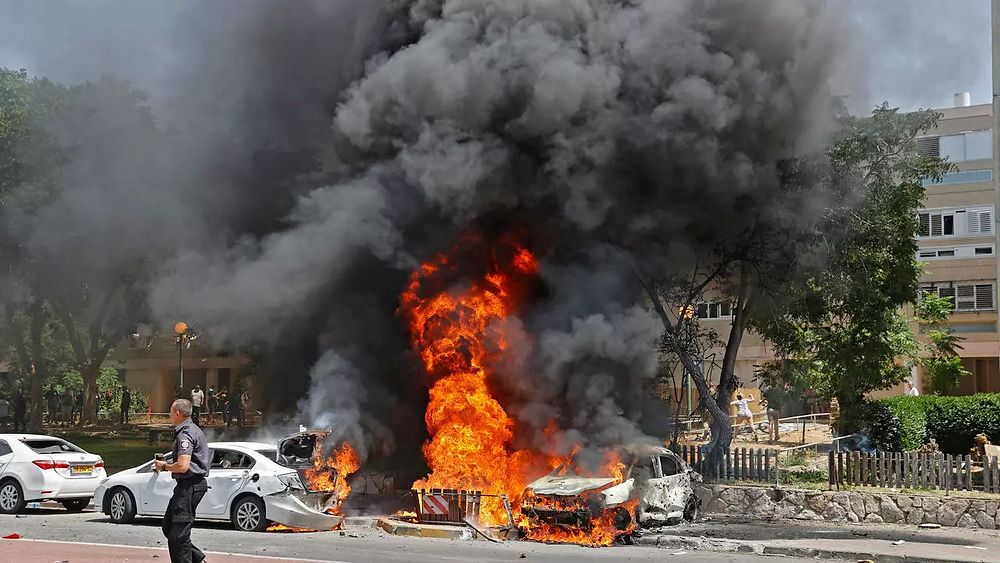 Vehicles ablaze after a rocket launched from the Gaza Strip landed in the Israeli city of Ashkelon