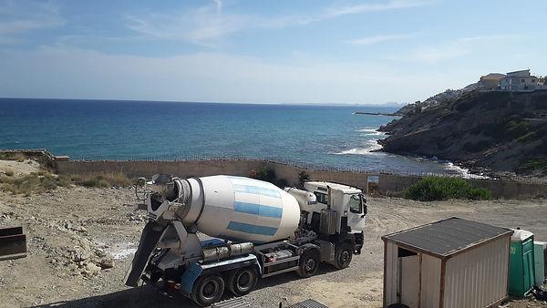 camion hormigonera hechando hormigon en la playa