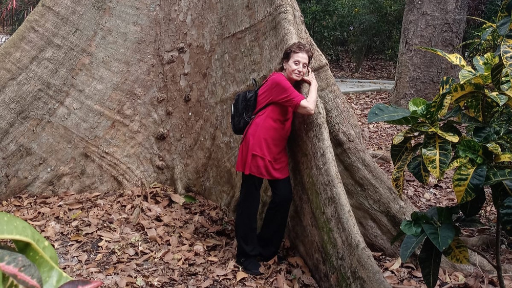 Nomi Bachar leaning on a large tree