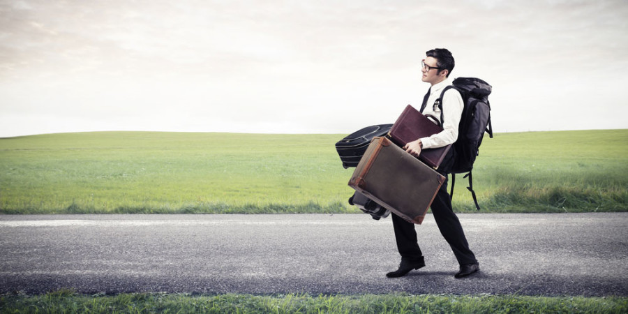 Man struggling to carry luggage on the road