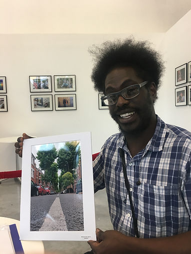 Wayne holds one of his photos at the opening of our photography group exhibition in 2019. This year Wayne and the other mentoring group participants have been connecting on WhatsApp and through a weekly contest run by volunteers