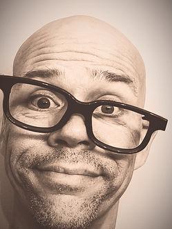 Portrait, man in tilted horn-rimed glasses,