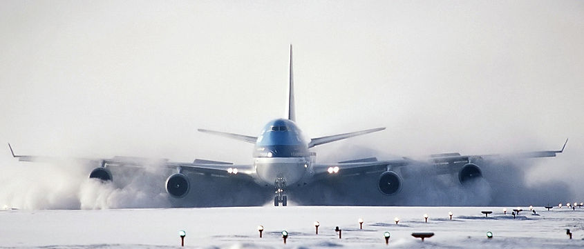 A Boeing 747-400 touches down at a snowy Sapporo airport