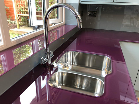 Aubergine worktop and window sil combined with grey glass splashbacks