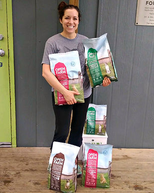 Pet Community Center employee holds bags of donated dog food