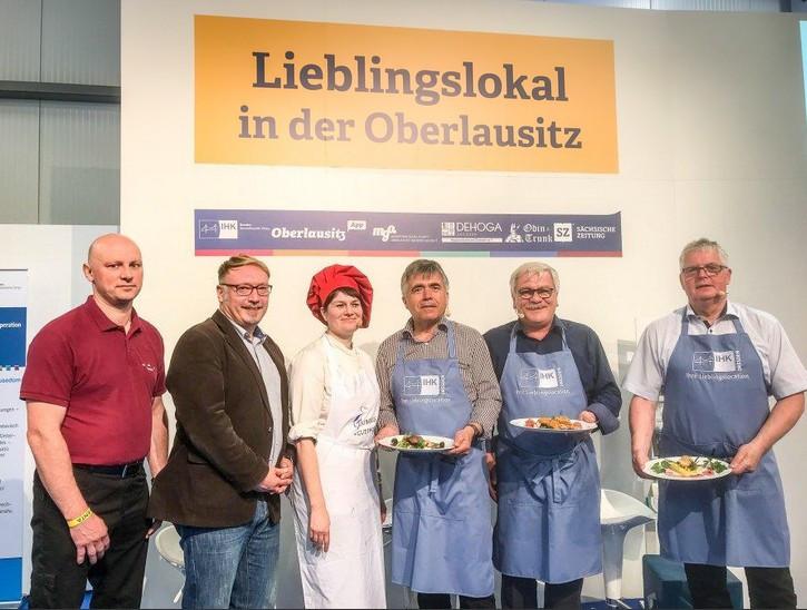 Kochshow auf der KONVENT'A 2018 in Löbau: (v.l.n.r.) Jan Schulze (Gewinner Lieblingslokal der Oberlausitz 2017, Hotel-Restaurant Sachsenstube in Lauta), Ronny Hausmann (Oberlausitz-App), Tina Weßollek (Logis-Hotel Gutshof L'Auberge Bischofswerda), Michael Harig (Landrat Bautzen), Dr. Detlef Hamann (Hauptgeschäftsführer IHK Dresden) und Bernd Lange (Landrat Görlitz). Bild: meeco Communication Services