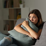 Scared teen at home embracing pillow sit