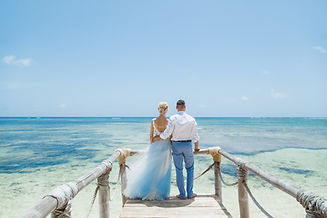 Newlyweds holding hands hugging at white sandy tropical caribbean beach landscape after we