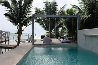 A beautiful pool with swinging chairs overlooking the Caribbean sea at a resort in Tulum,