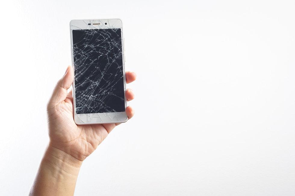 Man hand holding mobile phone with broken screen.jpg
