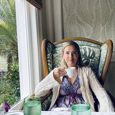Caroline drinking tea at a cafe, relaxing in a cozy chair