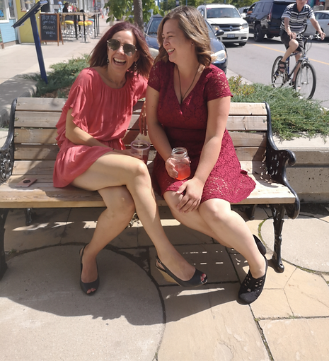 two ladies drinking kombucha in red dresses smiling