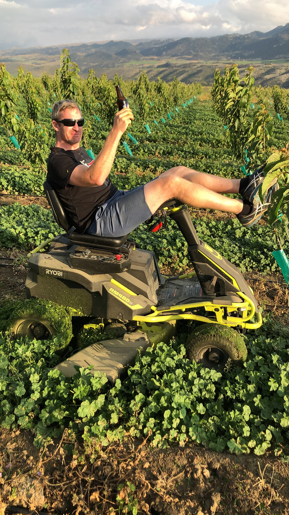 Euan enjoying a beer while mowing the rows