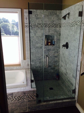Bath and frameless shower with natural stone and tile detail