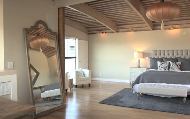 Large master bedroom with beamed ceiling and a sliding room divider