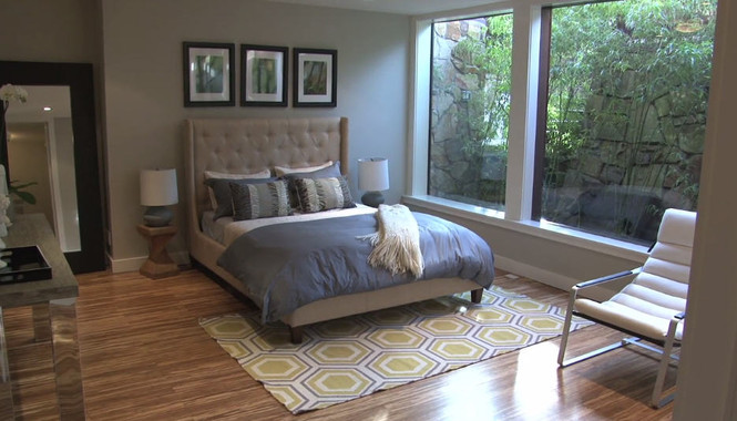 Master bedroom with large windows and hardwood flooring