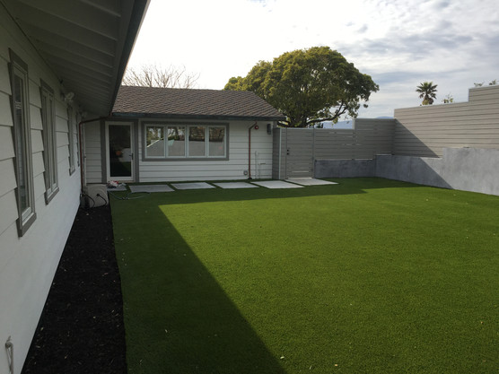 Lawn space with stone tile pathraised concrete garden beds