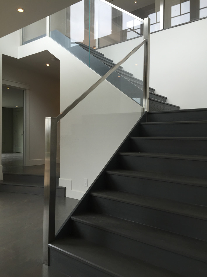 Half-turn staircase with glass panel railing
