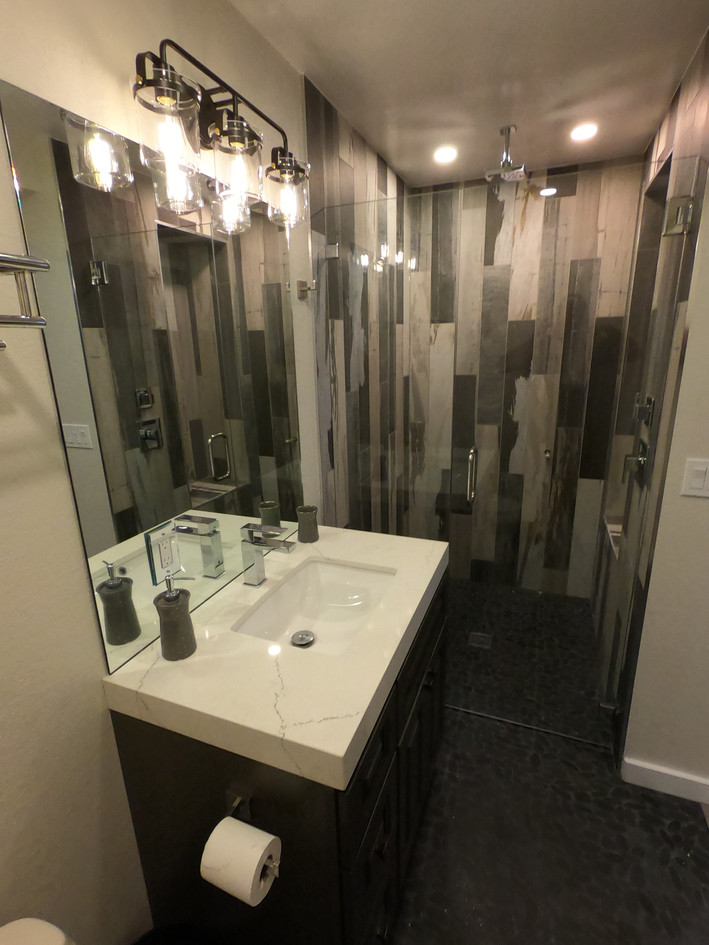 Small bathroom with variegated natural stone tiles