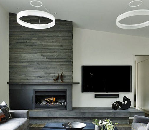 Large living space under a sloped ceiling with natural stone wall accents