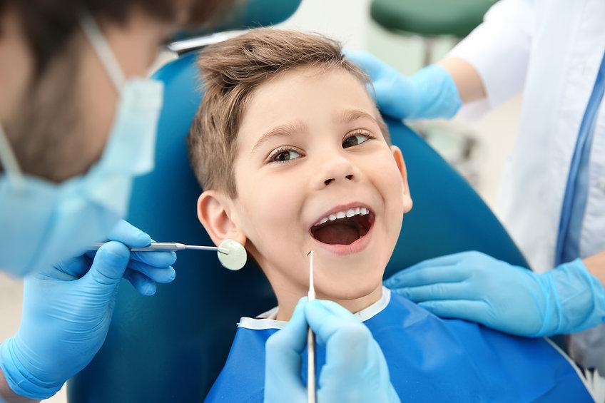 Dentist examining little boy's teeth in clinic.jpg