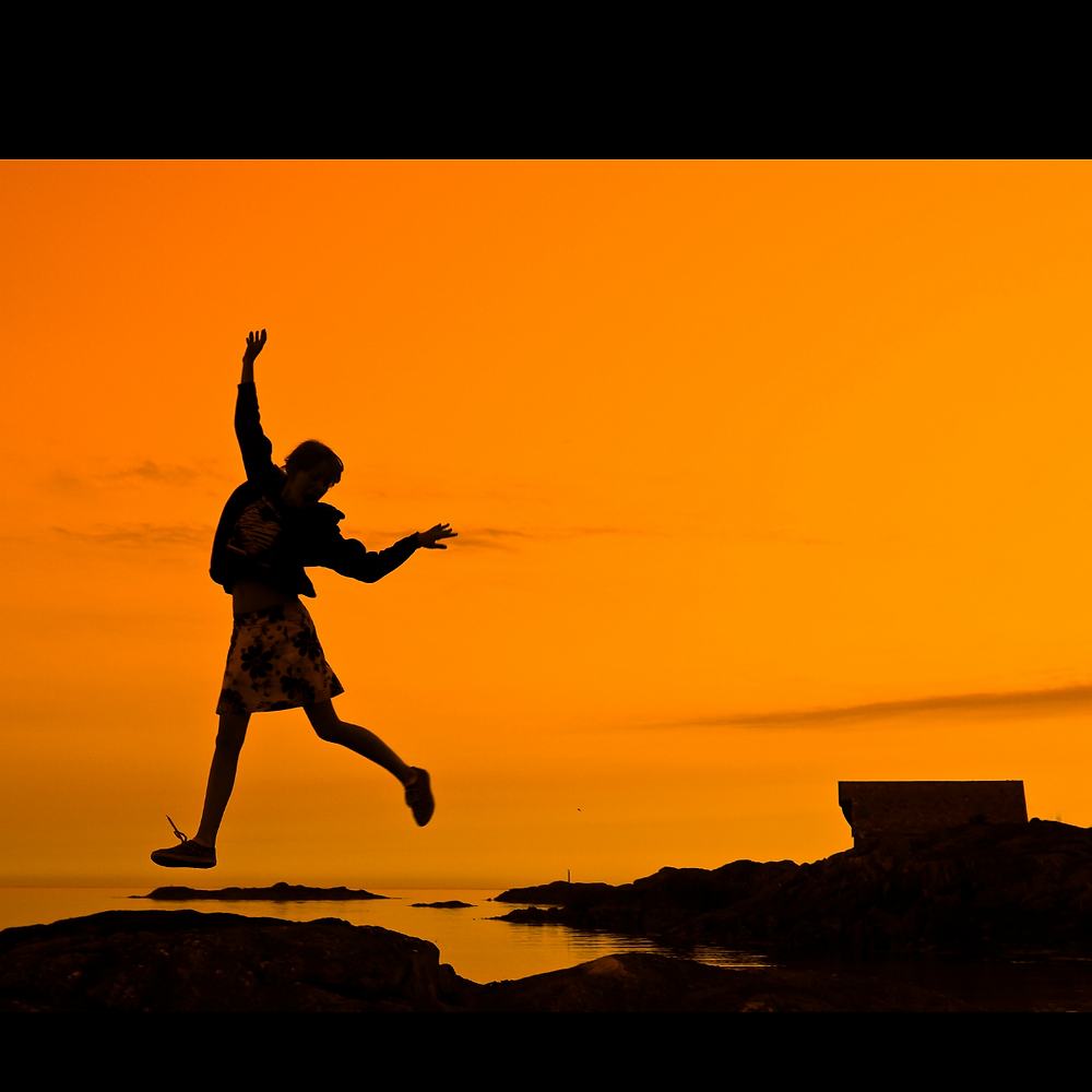 A person jumping with joy on a bed of rocks by the ocean