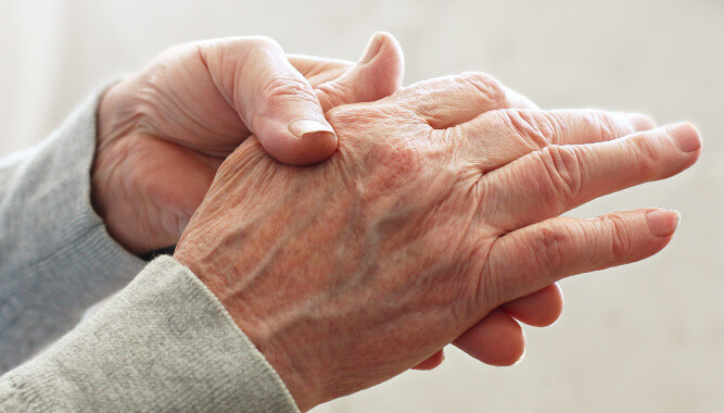 man wondering about what causes hand numbness rubs his palm