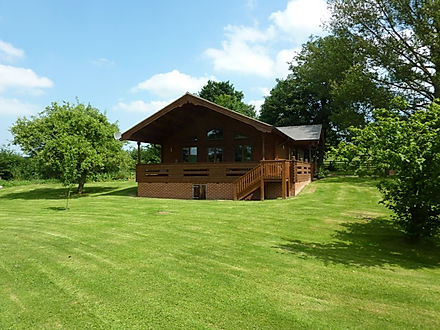 Large log cabin positioned in a private garden on the farm