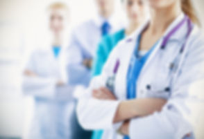 Attractive female doctor in front of medical group.jpg
