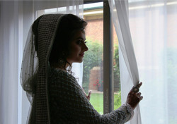 Bride looking out of the window in her wedding dress