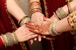 bridesmaids making a promise by a show of mehndi henna tattooed hands