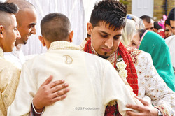 The groom meeting his brother in law and hugging during baraat