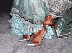 Bride in teal wedding dress putting on designer shoes