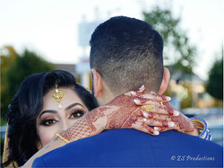 Bride peering over grooms shoulder showing her eyes and eye make up and hand henna mehndi