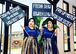 bridesmaids holding up tongue in cheek signs asking for groom to pay