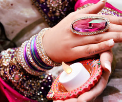 Bride holding a candle and showing her bridal ring, bangles and hand jewellery