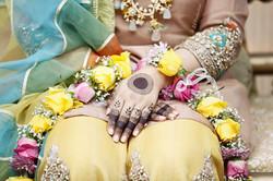 Mehndi bride showing her henna mehndi hand tattoo and flower garland
