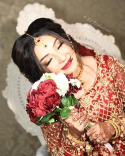 beautiful Asian desi bride holding bouquet of flowers