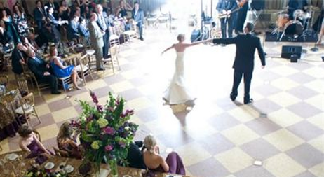 bride and groom dancing on a checkered floor at their wedding reception