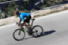 man wearing a blue top and a red helmet going down hill on a bike