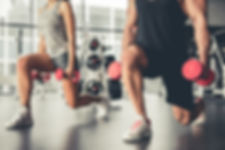 A man and a woman lifting weight in a gym
