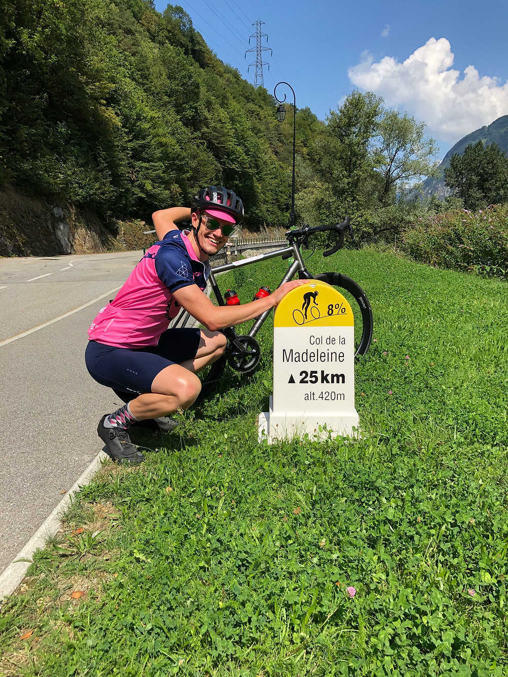 cyclist beside a sign at the bottom of a long mountain climb
