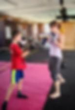 a woman coach teaching boxing to a kid