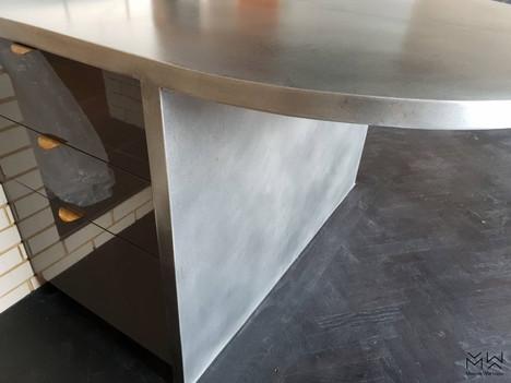 Curved, lightly aged zinc bar