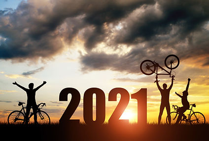 Silhouette of cyclists with bicycles at sunset. Forward to the New Year 2021. Holiday conc